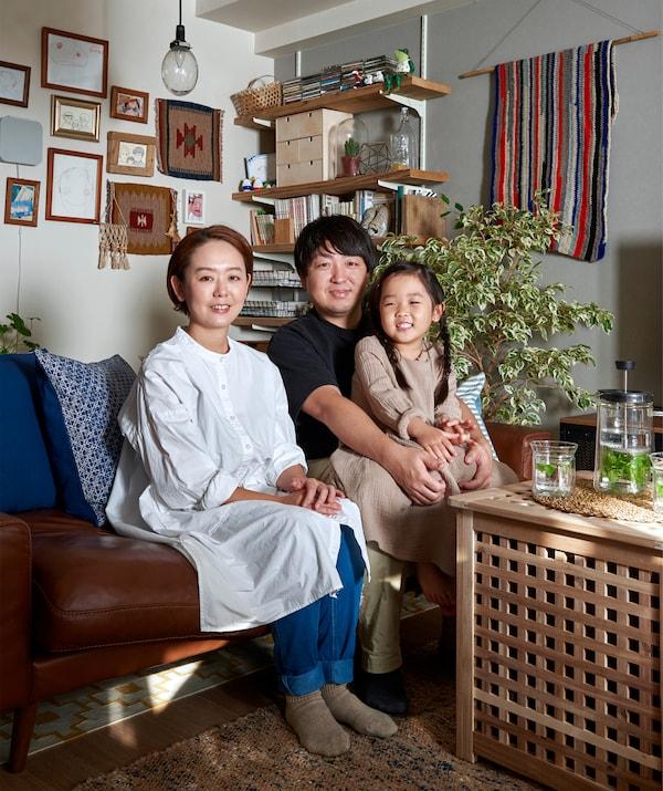 Mieko、Kenta和他们的女儿一起坐在沙发上的照片。