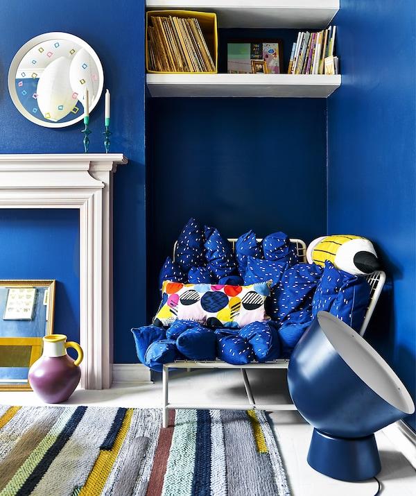 明快的蓝色客厅里摆放着沙发、超大尺寸的灯具,并铺有地毯。