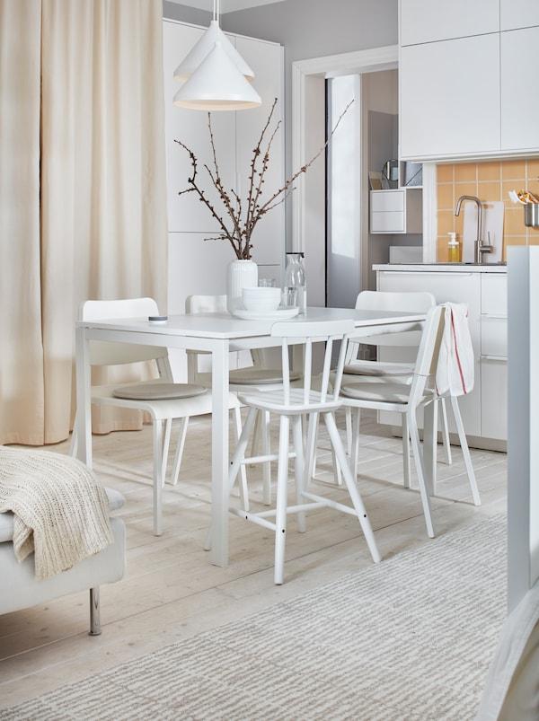 明亮的白色一室公寓里,摆放着一张MELLTORP 麦托 桌子和TEODORES 帝奥多斯 椅子,中间有一个小厨房和一张床。