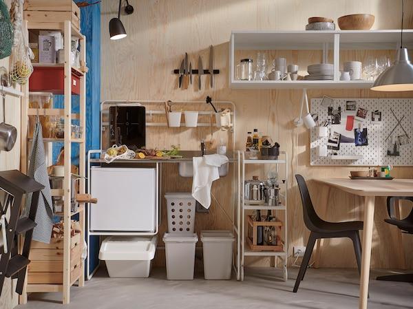 明亮的小厨房里设有 SUNNERSTA 苏纳思 独立橱柜、灰色垃圾桶、松木储物系列和黑色椅子。