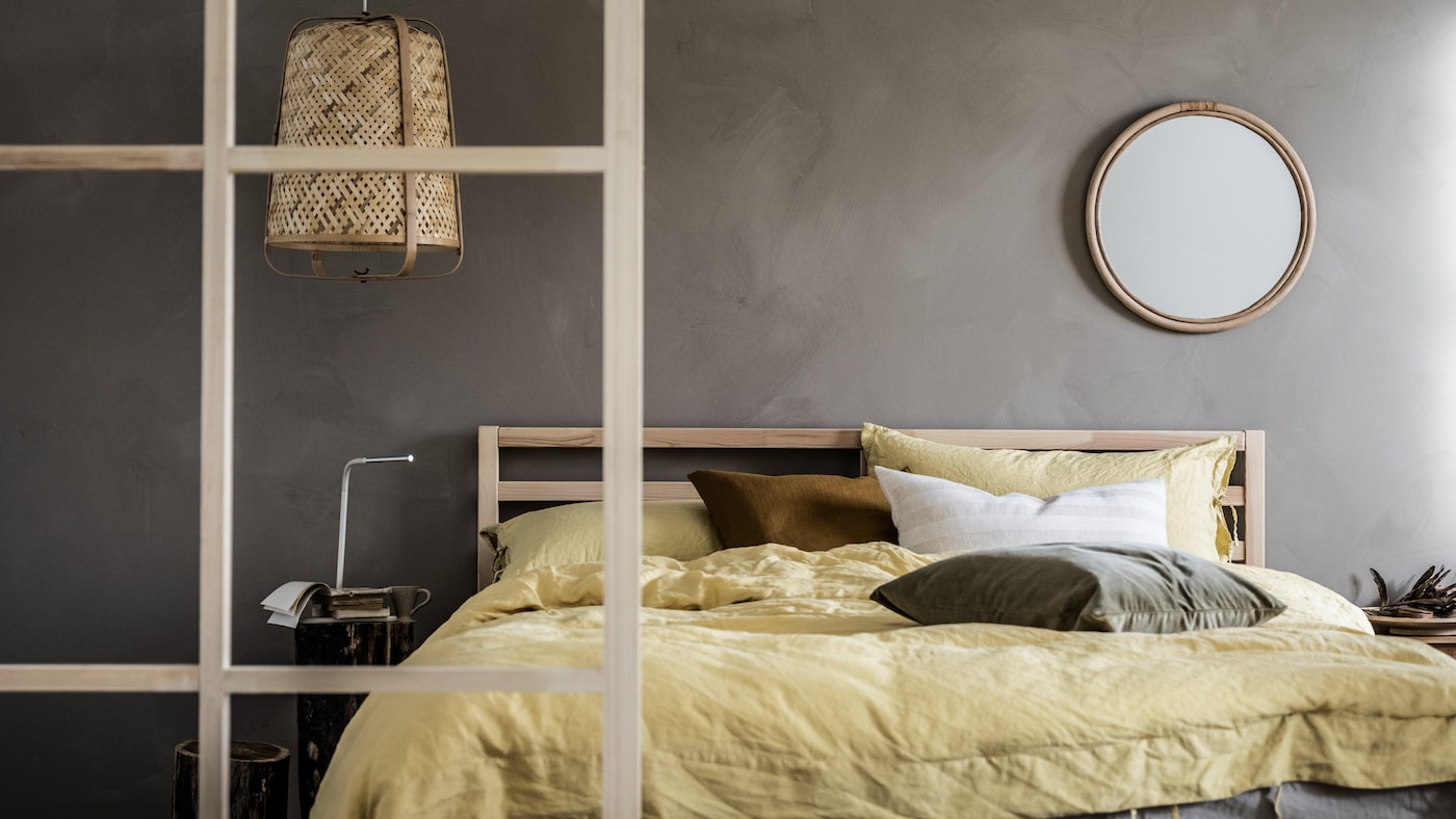 Minimalistic bedroom with grey walls and toned-down colour scheme, wood details, a TARVA double bed, and a KNIXHULT lamp.
