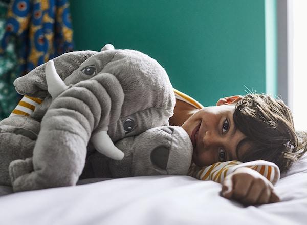 墨绿色的卧室里,一个小男孩开心地躺在床上,怀里抱着一只灰色的 JÄTTESTOR 雅特斯托 大象毛绒玩具。