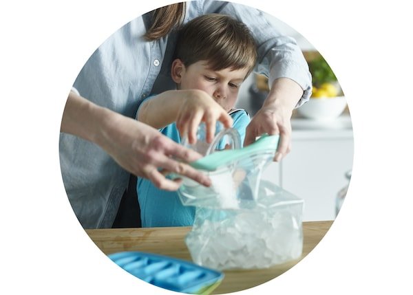 Mother and son are filling a ISTAD plastic bags with ice cubes.