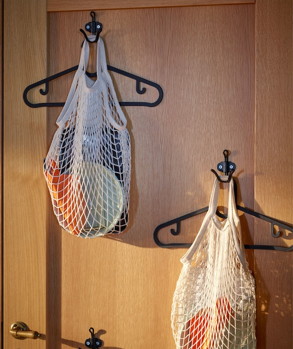 木材前门内零散地安装着几个挂钩。每个挂钩上都挂着衣架和装有晚餐用具的网袋。