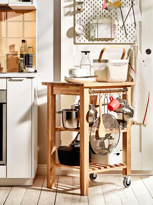 木制BEKVÄM 贝卡姆 手推车上,摆放着锅具和其他厨房配件,宛如延伸的厨房工作台。