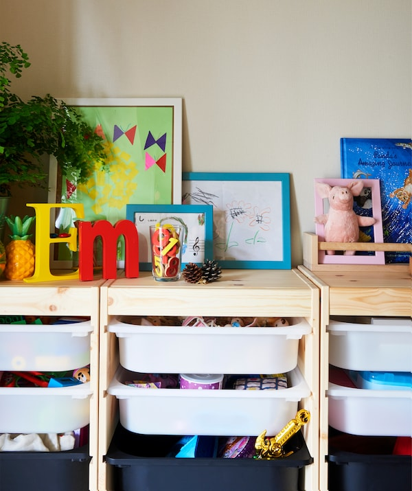 木质储藏柜框架上方摆着植物、图片和书,内部的塑料托盘上存放着玩具。