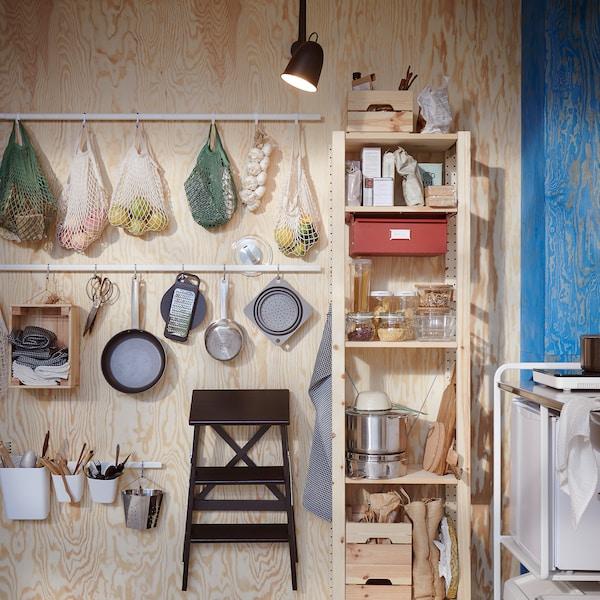 木质墙面上固定有附钩挂杆,上面挂有装着水果的网袋、厨用器具和一个踏脚凳。
