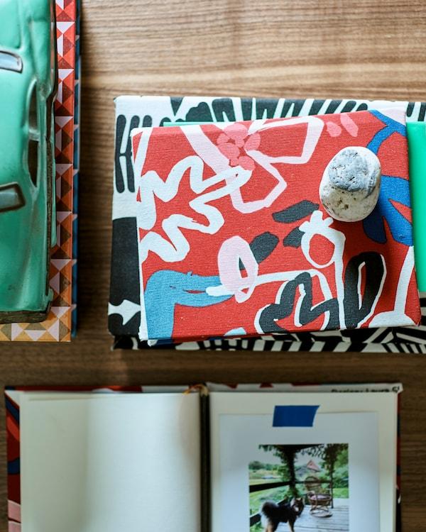 木桌上放置着几本书,饰有图案的布料用作封面,旁边还有一个绿色玩具车。一本翻开的书,上面贴有一张照片。