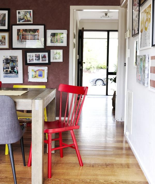 木桌四周摆放着彩色的椅子,暗红色墙面上展示着图片,一扇门通往大厅。