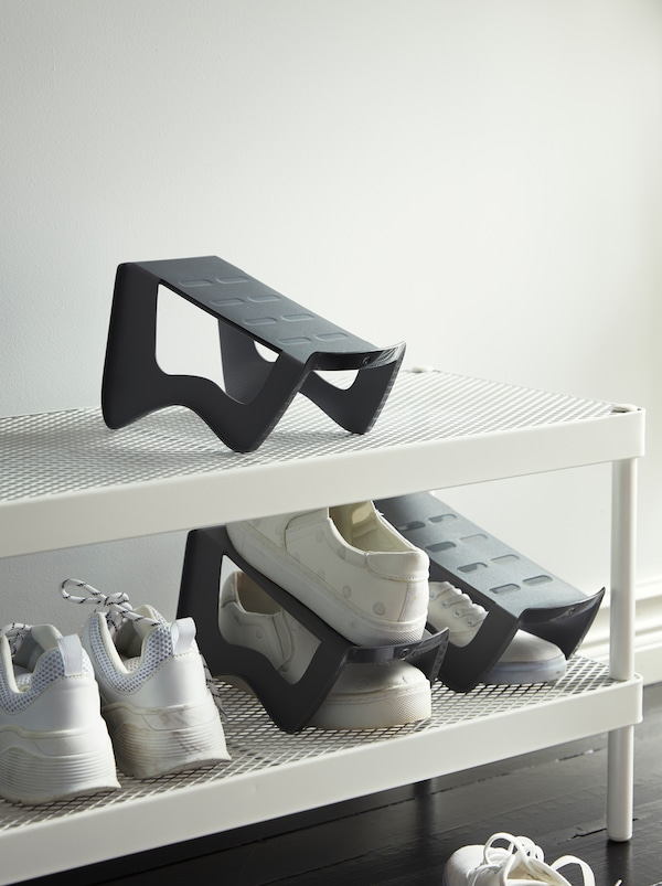 MURVEL shoe organisers maximise the use of space on a white MACKAPÄR shoe rack, holding pairs of white sneakers.