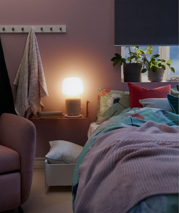 Narrow bedside shelf holding a WiFi speaker table lamp spreading a soft light over a dimly lit bedroom.