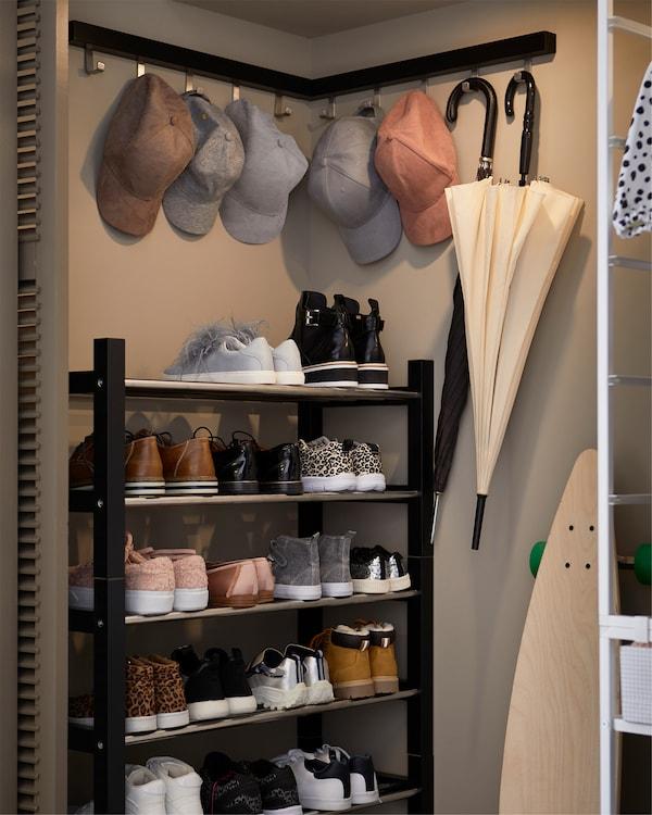 内置衣柜的一角,几个黑色不锈钢鞋架叠放在一起,形成了更高的鞋架。