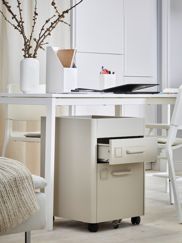 Next to a bed stands a white table with work accessories scattered on it and an IDÅSEN drawer unit placed underneath.