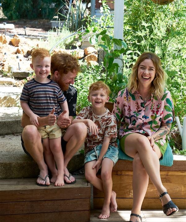 Nici和Ben以及他们的两个孩子坐在花园里的木板上。