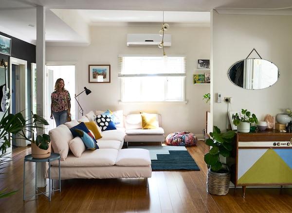Nici正走进一间白色客厅,里面配有大型淡粉色沙发、蓝色地毯和复古餐边柜。