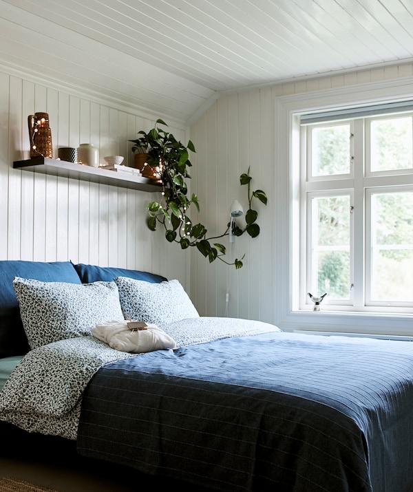 农舍风格的卧室配有白色木料镶板,床上放着蓝色床上用品,上方的墙搁板用于存放和展示物品。