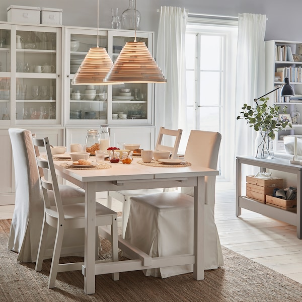 NORDVIKEN extendable table and chairs stand in a breakfast setting. Lit pendant lamps give warm lighting from above.
