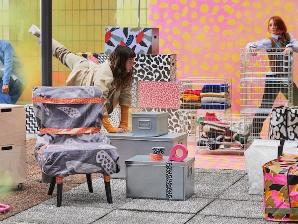 OMBYTE 欧姆比特 搬家盒采用饰有醒目图案的硬纸板、金属和铁丝制成。用灰色毯子将椅子包裹起来,并用包装带固定。