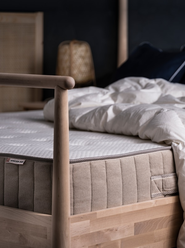 On a GJÖRA birch bed in a softly lit bedroom lie a VATNESTRÖM mattress and a duvet, both without additional bed linen.