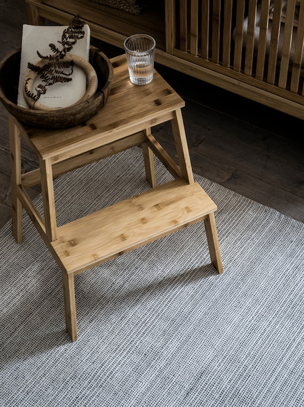 On a TIPHEDE recycled-cotton rug stands a TENHULT bamboo step stool, on it a glass of water and a small basket.