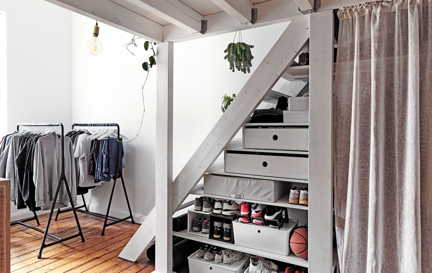 Open clothes rails and storage boxes under a flight of stairs.