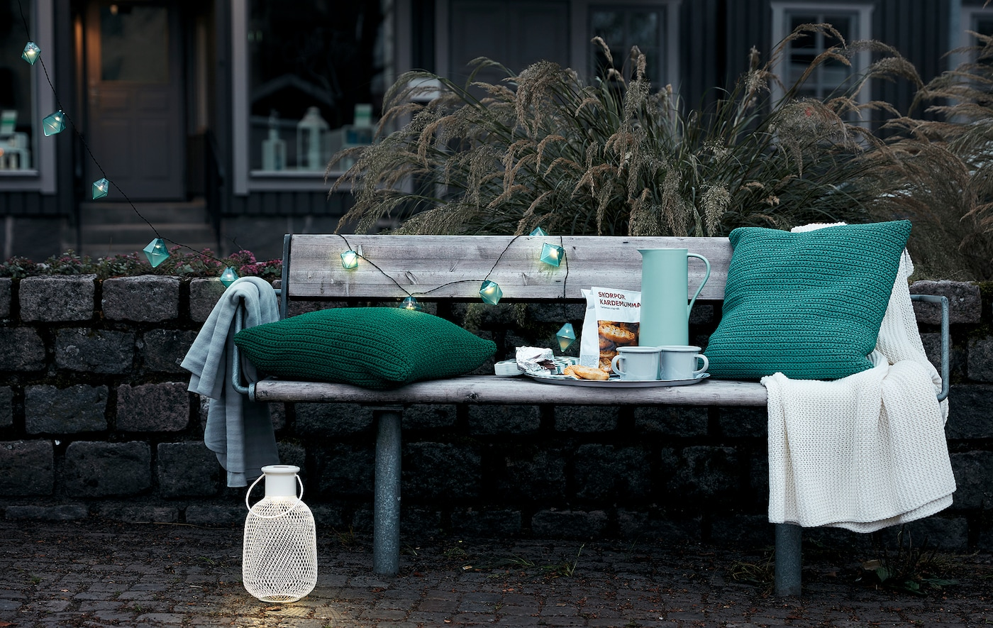 Outdoor, early-evening city setting with a public bench set with a coffee tray, cushions, a throw and decorative lighting.