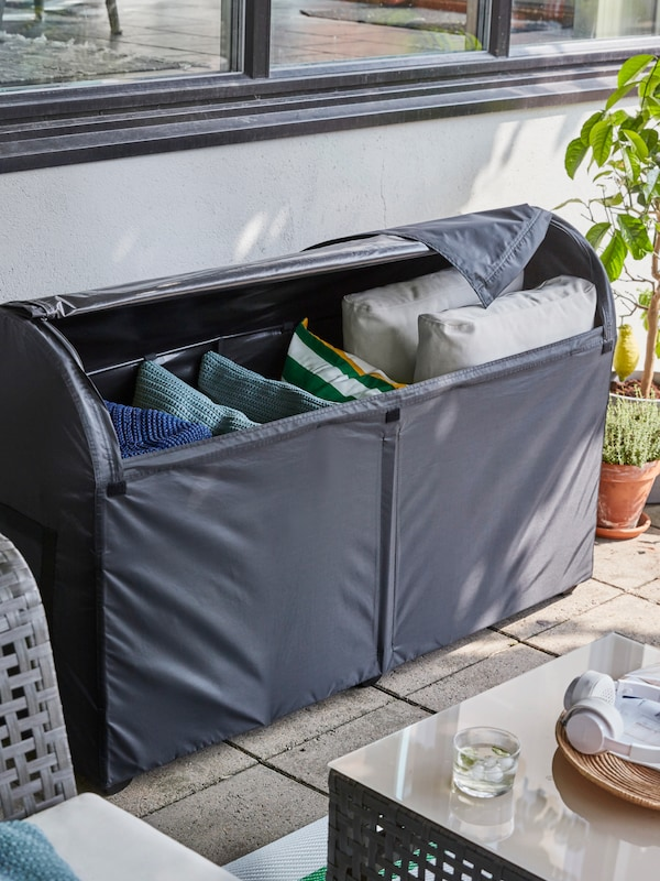 Outdoor storage in dark grey, containing larger and smaller cushions, on a terrace beside some potted plants.