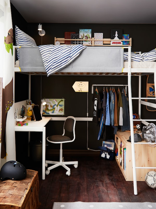 Part of a children's room made up of a VITVAL loft bed and below it a study corner, a row of clothes on hangers, and storage.