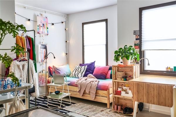 配备多种家具的小型公寓,如搁板、晒衣架、由靠垫制成的沙发和两张矮折叠床。