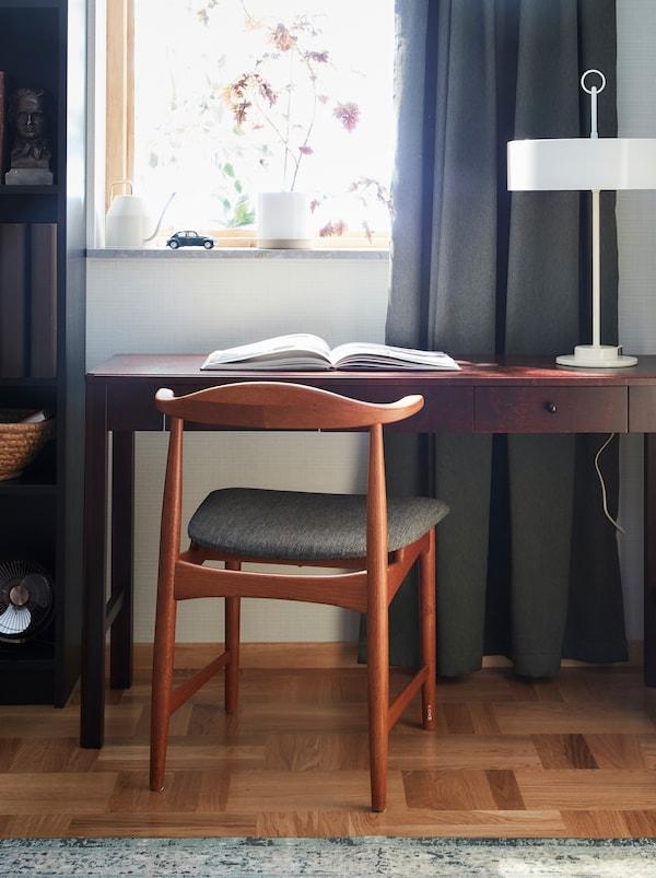 配布料座椅的橡木DANSKE 丹斯克 椅子是宜家60年代的一款设计,后面是一张深色木桌子。