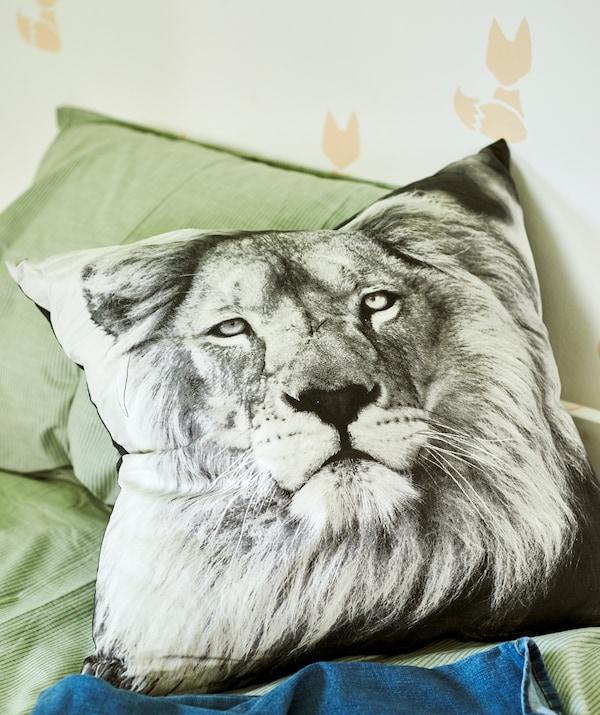 配有绿色床上用品的床上放着一个印有黑白狮子图案的靠垫,墙壁上印有狐狸图案。