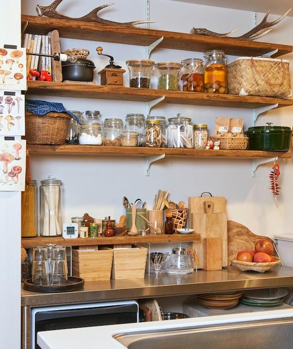 配有木盒和木板的金属操作台面上方,一个木质搁板上放着盛有配料和腌菜的罐子。