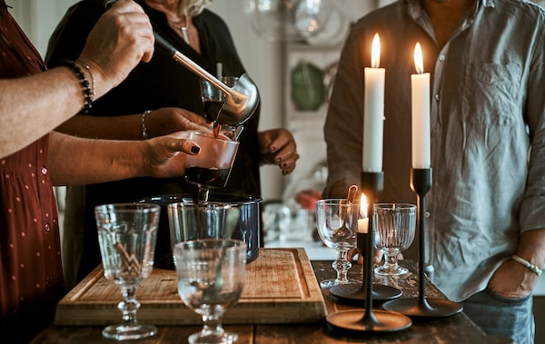 People stood at a kitchen island with glasses and lit candles and a pot of hot punch, one is ladling the drink into a glass.