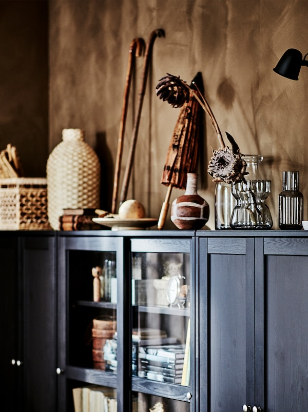 Personal items from travels, things in natural materials, and glass vases with flowers on top of a dark brown HAVSTA cabinet.