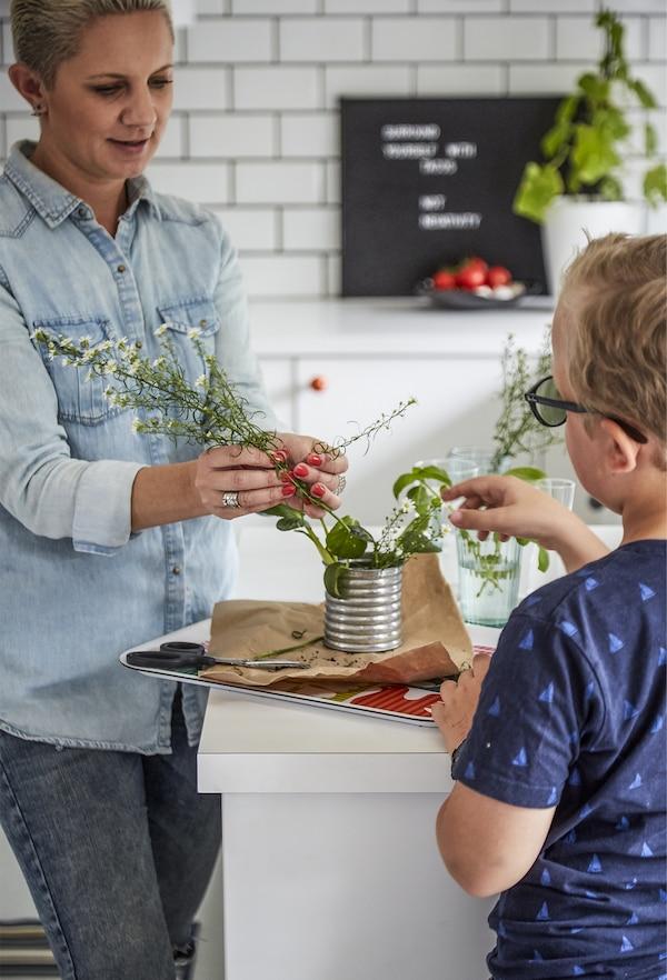 Pia和Liam将植物枝条放入罐子里。