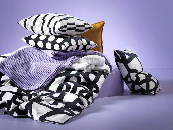 Pillows, with pillow cases in various black and white designs.