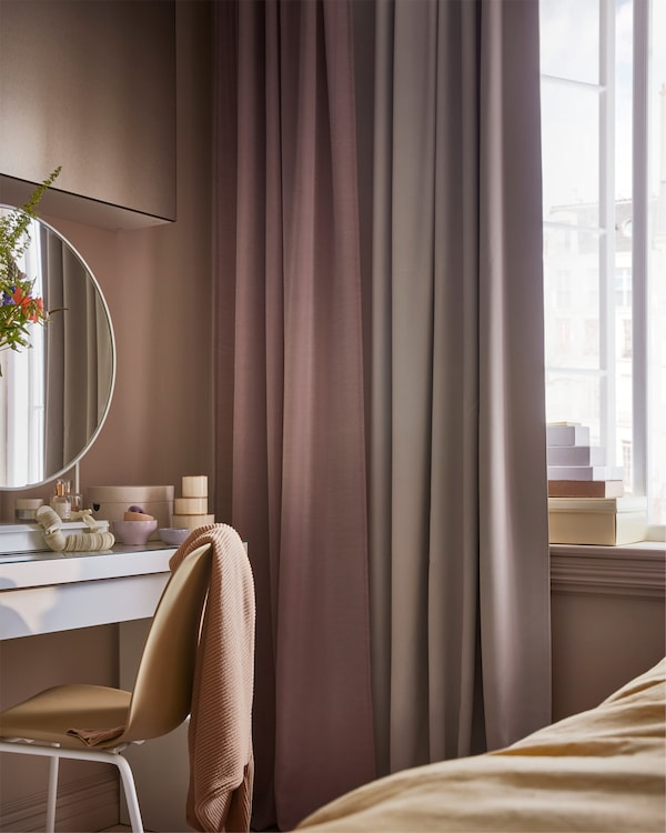 Pink and grey curtains, a yellow chair, and white dressing table with a white table mirror and small boxes standing on it.