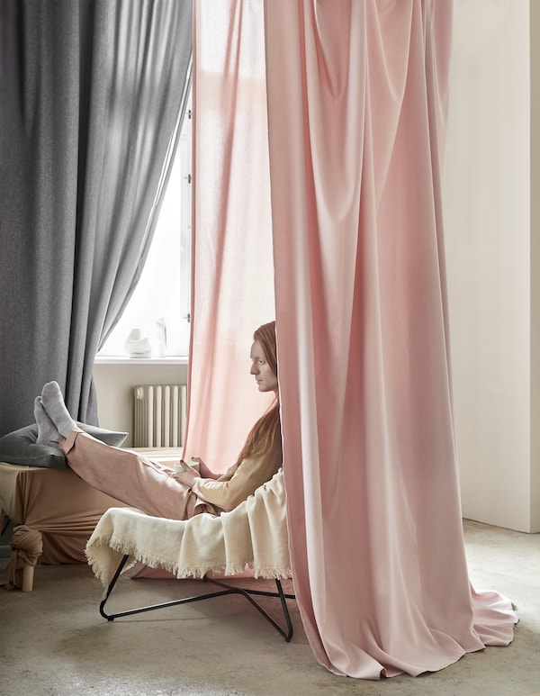 Pink and grey curtains hanging around a man sitting in a chair.