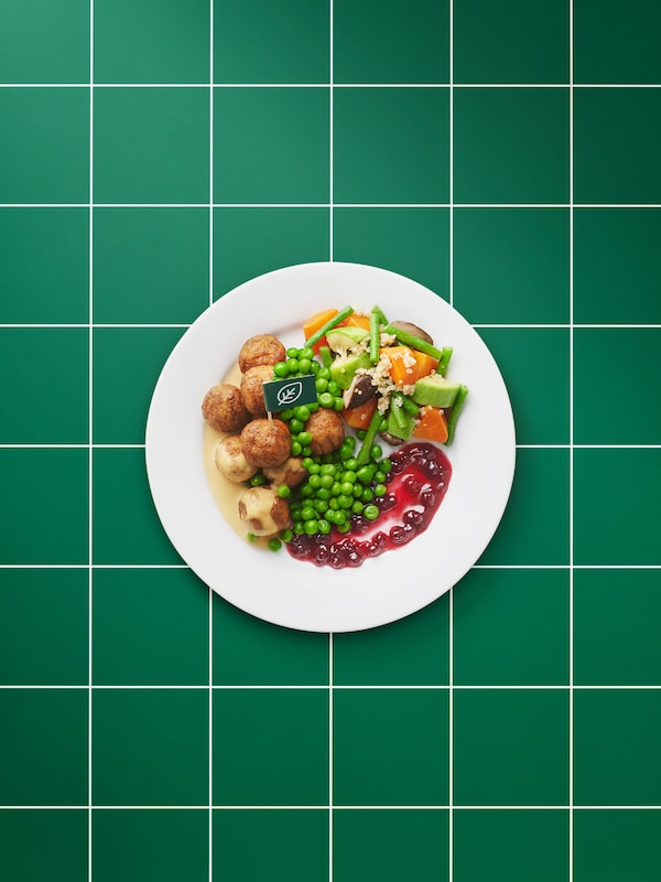 Plain white plate of plant-based meatballs, brown sauce, mashed potatoes, lingonberry jam, green peas and a sprig of parsley.