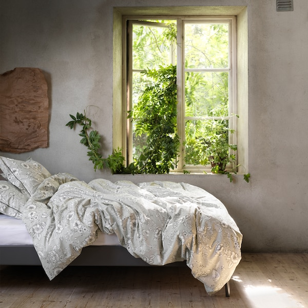 PRAKTBRÄCKA quilt cover and pillowcase in a traditional floral pattern seen in a cosy bed next to an open window.