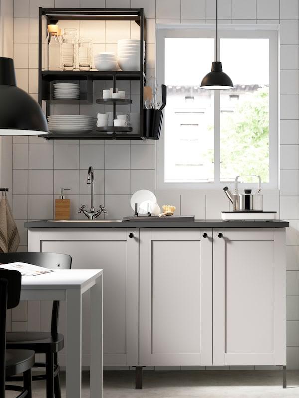 铺设白色瓷砖的厨房采光良好,窗户旁边摆放着带白色前板和黑色搁板的ENHET 安纳特 厨房家具。