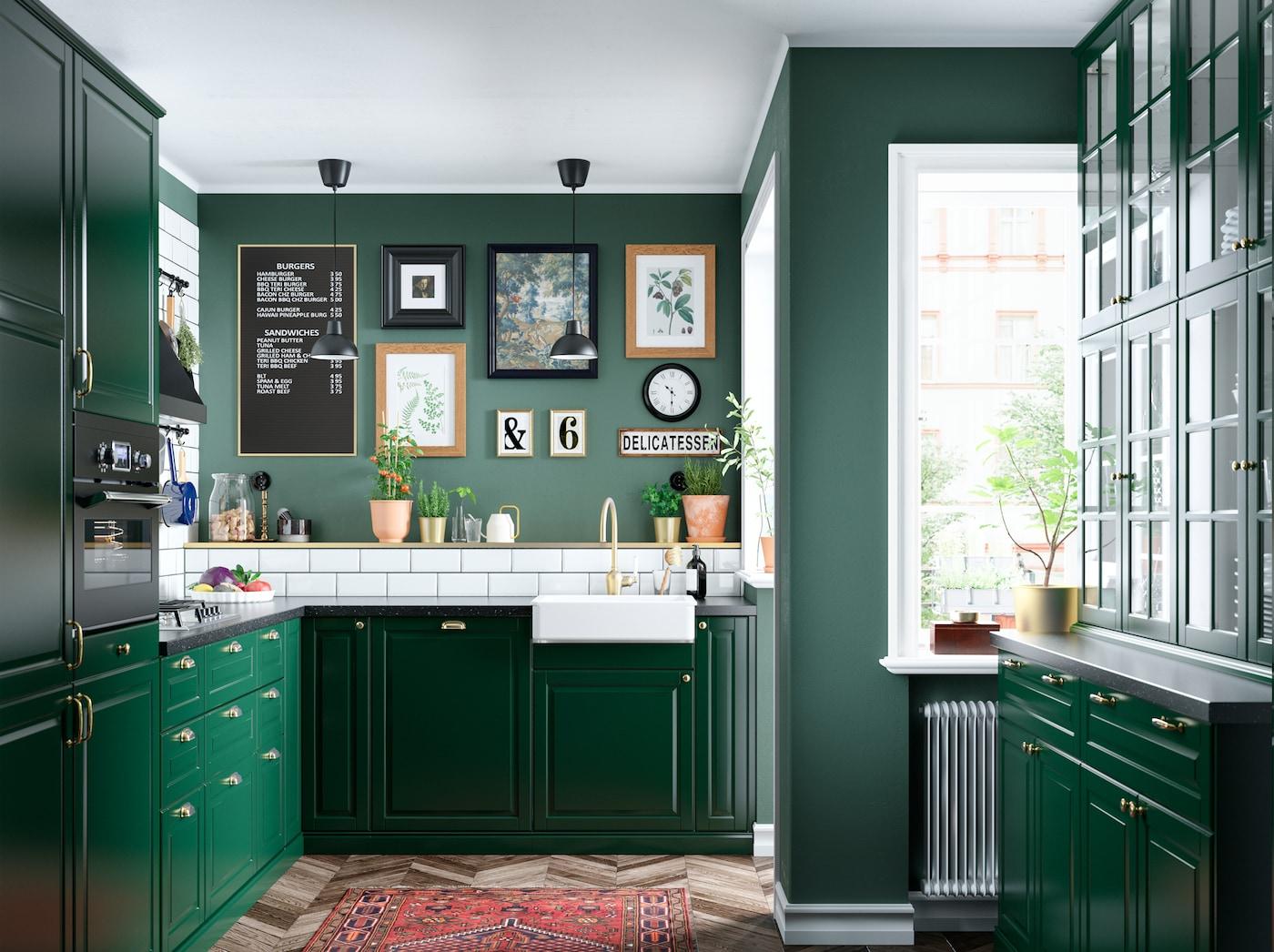 铺着白色瓷砖的深绿色厨房配有玻璃柜门和黄铜色混合型水龙头,图片墙上挂着各种各样的画框。