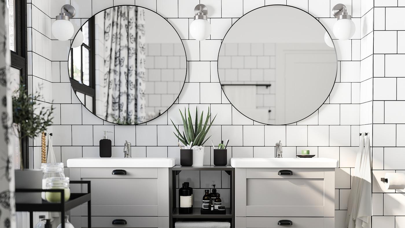 铺着白色瓷砖的浴室,带两面圆镜,两个灰白色洗脸池,一架黑色手推车和三盏壁灯。