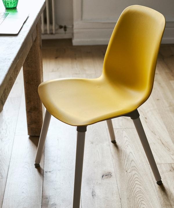 铺着木地板的房间里摆着一把带木支腿的黄色塑料餐椅和一张木餐桌。