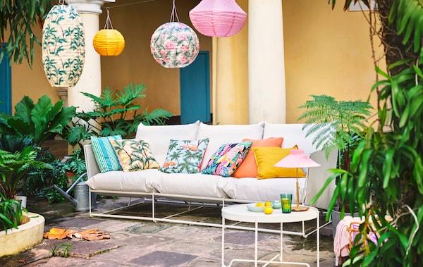 铺着天然石材的露台上摆着白色沙发。沙发上的靠垫和上方的吊灯均采用鲜艳的颜色和图案。