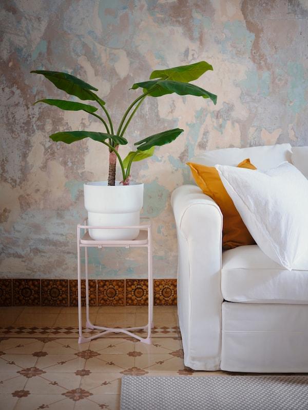 浅粉色植物架上摆放着盆栽植物,旁边的白色沙发上放置着靠枕。