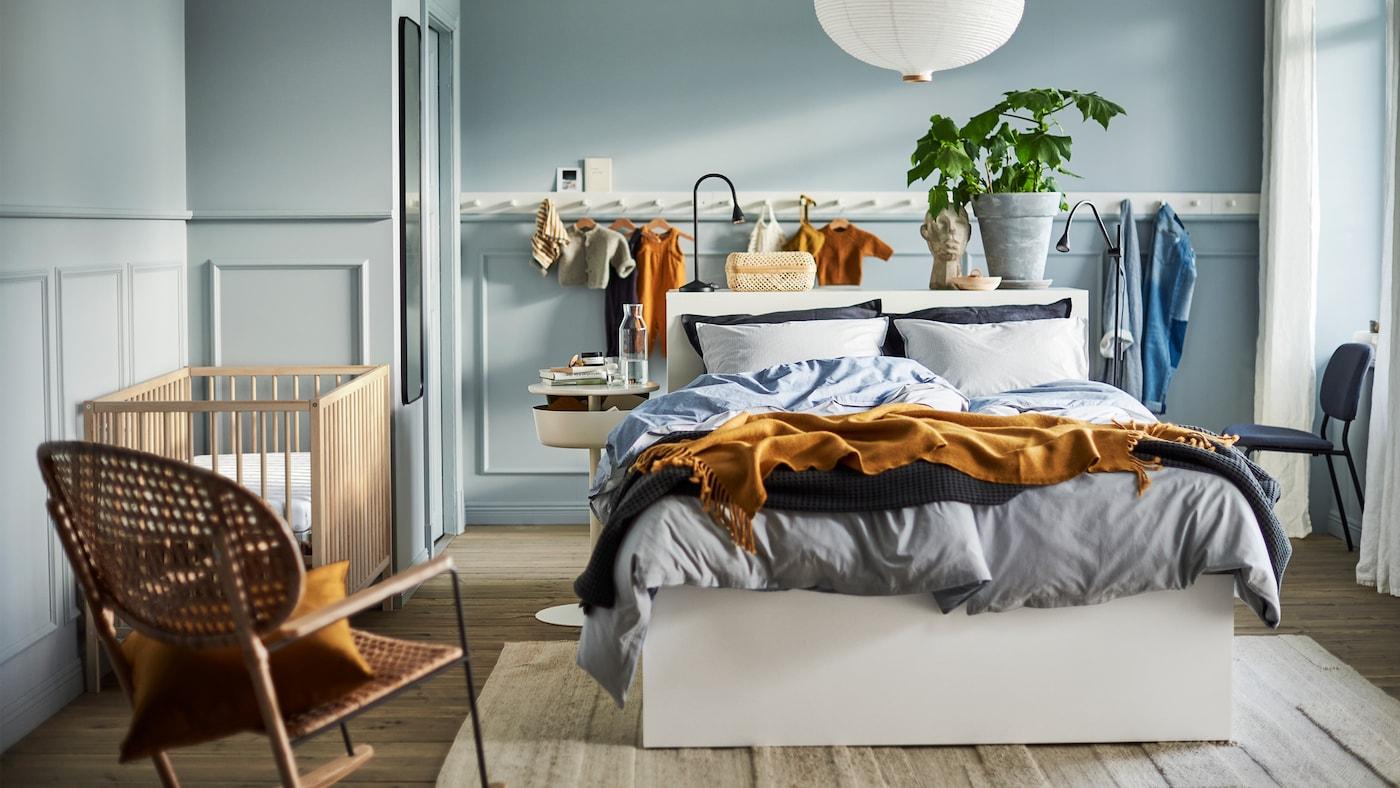 浅蓝色调的卧室,配一张白色的床、一盏白色的灯、一排白色的挂钩,一张藤制摇椅和一张SNIGLAR 辛格莱 婴儿床。