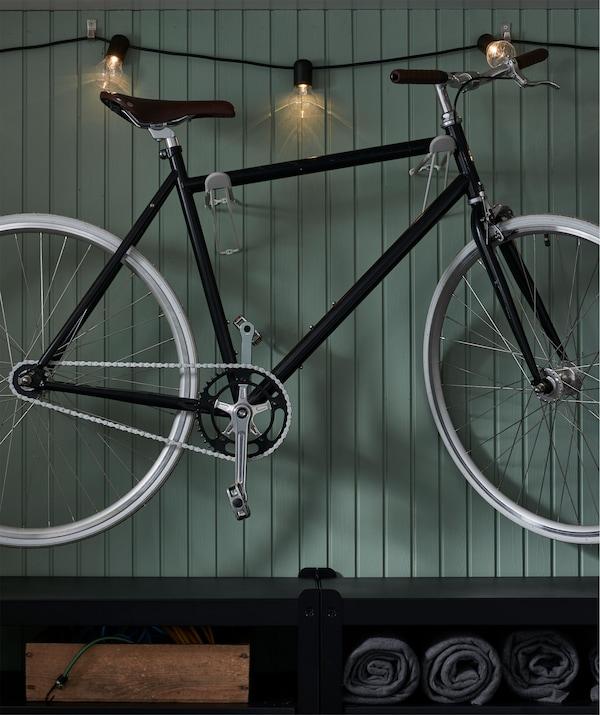 墙面上有一部挂钩挂着的自行车,灯串沿墙排布,点亮了整面墙,下方则是一个搁架单元。