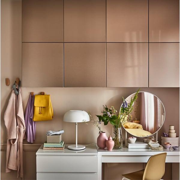 墙上安装有浅青铜效果的门,一款白色梳妆台,一款白色圆形镜子和一些壁挂式竹挂钩。