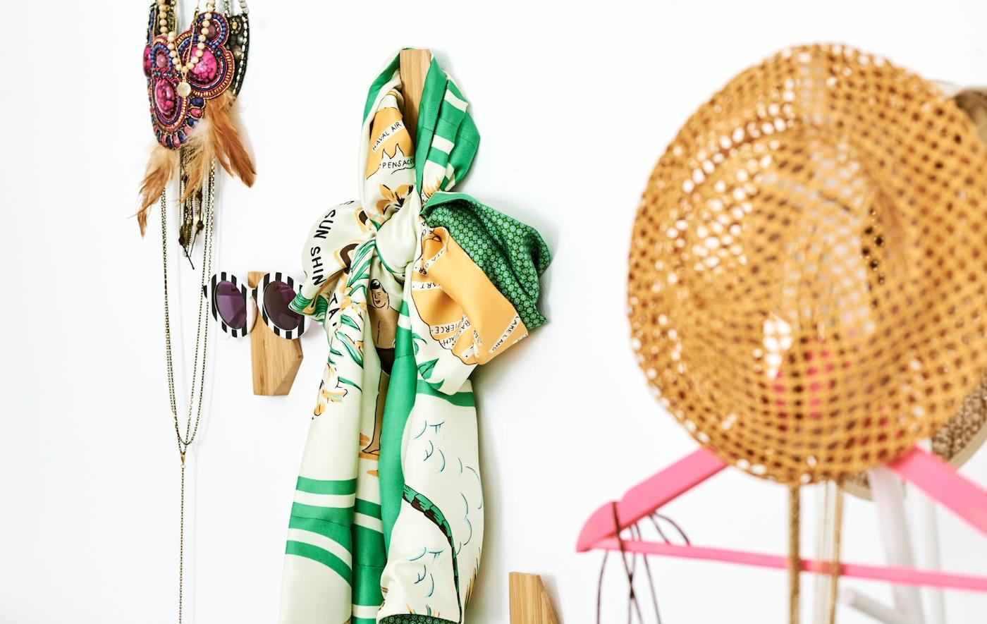 墙上挂有不对称造型的竹材挂钩,每个挂钩上都挂着一个不同的衣物配饰——太阳眼镜、围巾、项链和草帽。